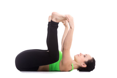 Woman doing happy baby yoga pose