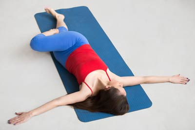 Woman lying on yoga mat doing yoga pose